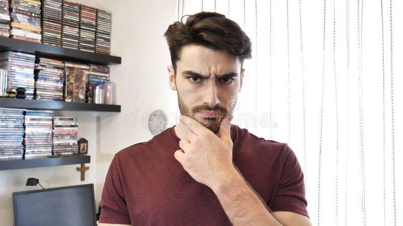 Verwirrter junger Mann, der sein Kinn, Kamera betrachtend verkratzt stockbild