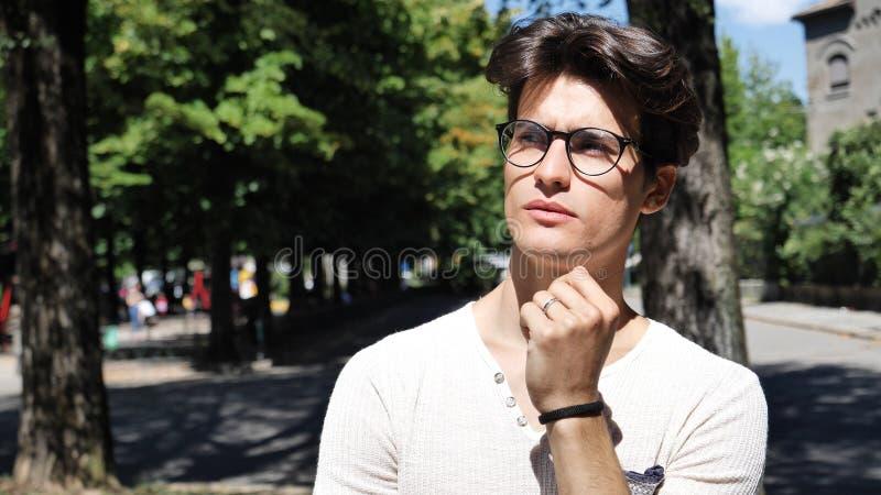 Verwirrter junger Mann, der seinen Kopf, oben schauend verkratzt stockfotografie
