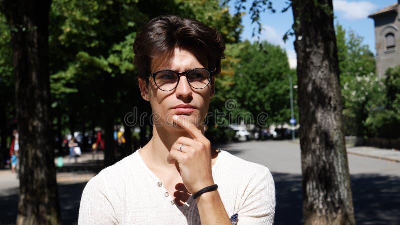 Verwirrter junger Mann, der seinen Kopf, oben schauend verkratzt stockfotos