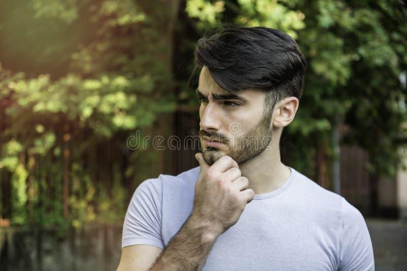 Verwirrter junger Mann, der seinen Kopf, oben schauend verkratzt lizenzfreie stockbilder