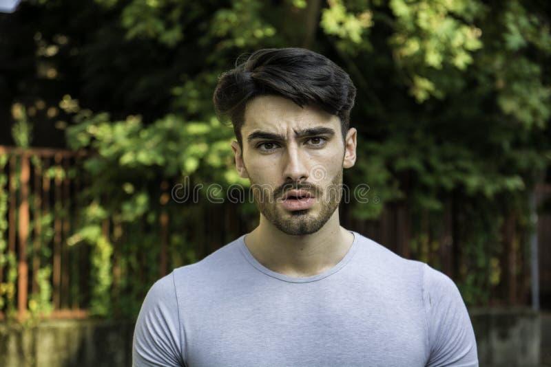 Verwirrter junger Mann, der seinen Kopf, oben schauend verkratzt lizenzfreies stockbild