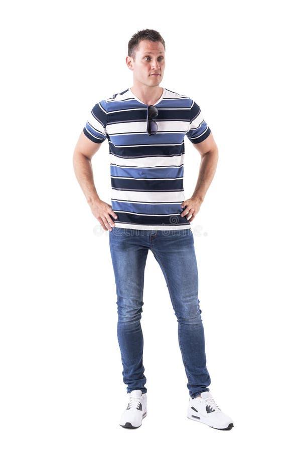 Verwirrter junger Mann in der zufälligen Kleidung mit den Händen auf den Hüften, die weg zweifelhaft schauen stockfotos