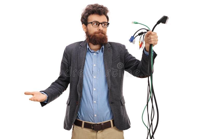 Verwirrter Kerl, der verschiedene Arten von elektronischen Kabeln betrachtet lizenzfreie stockbilder