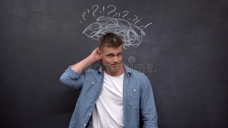 Verwirrter männlicher Kratzkopf gegen Tafel, Mangel an Erfahrung, Lösung stockbilder