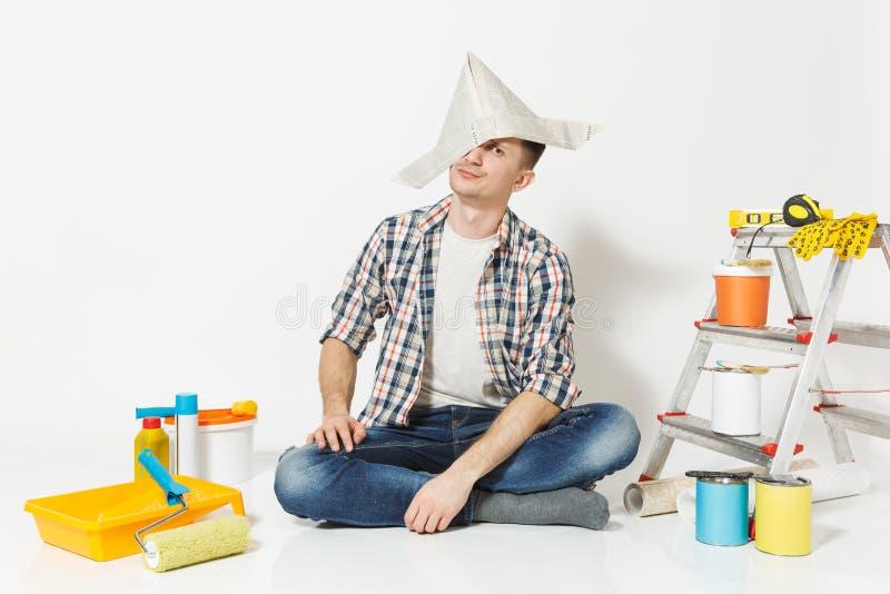 Verwirrter müder Mann im Zeitungshut, der auf das Auge, sitzend auf Boden mit Instrumenten für die Erneuerungswohnung lokalisiert lizenzfreies stockbild