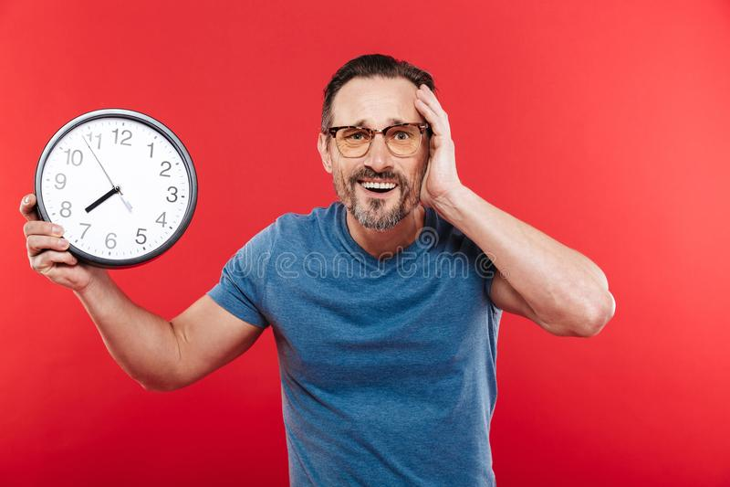 Verwirrter Mann in der bunten Sonnenbrille, die Uhr hält stockfotografie
