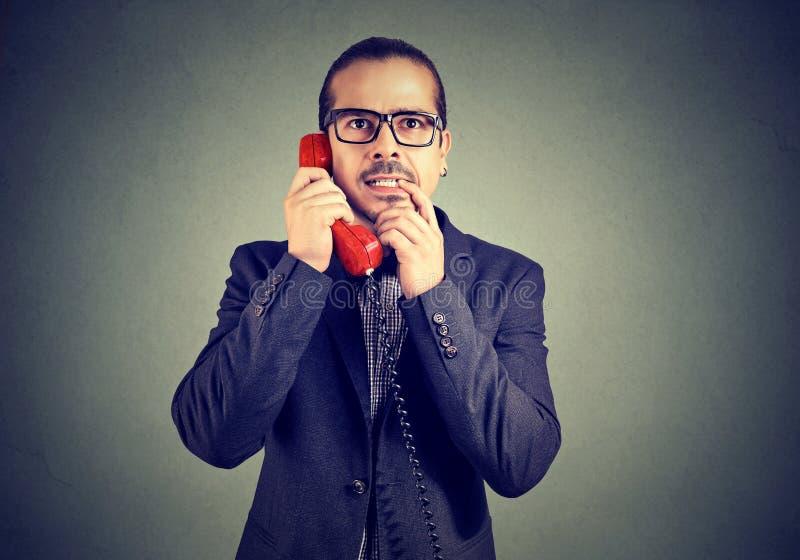 Verwirrter Mann, der an einem Telefon spricht stockbilder