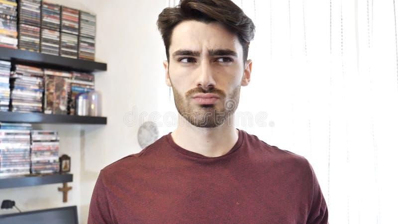 Verwirrter oder zweifelhafter junger Mann, der oben schaut lizenzfreie stockbilder