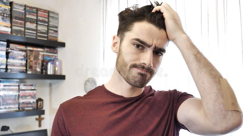 Verwirrter oder zweifelhafter junger Mann, der sein Kinn verkratzt stockbilder