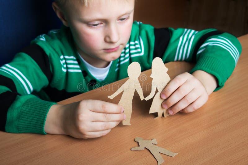 Verwirrtes Kind mit Papierfamilie lizenzfreie stockfotos