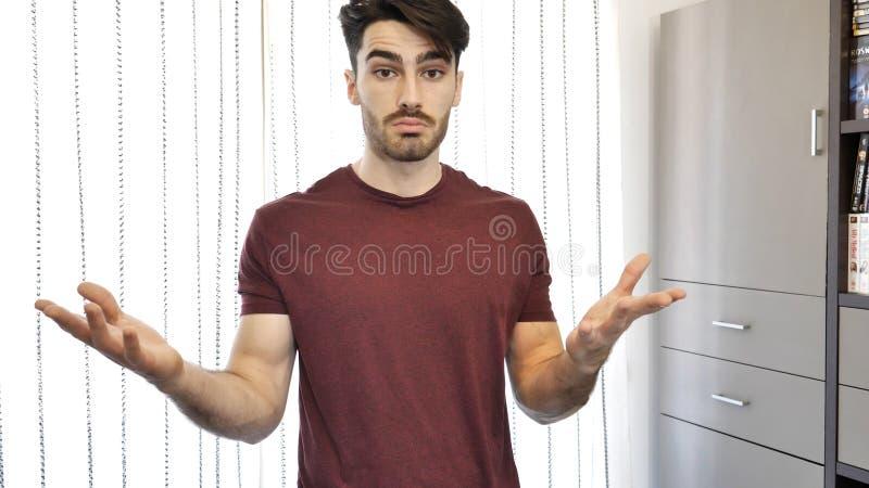 Verwirrtes oder zweifelhaftes Zucken des jungen Mannes lizenzfreies stockbild