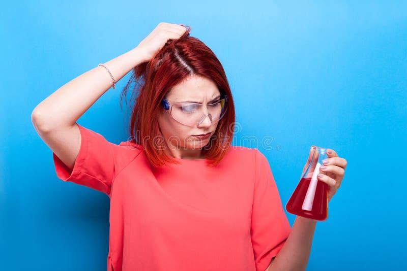 Verwirrtes schönes Sonderlingsmädchen mit einem Rohr der roten Flüssigkeit in ihrem ha stockbilder