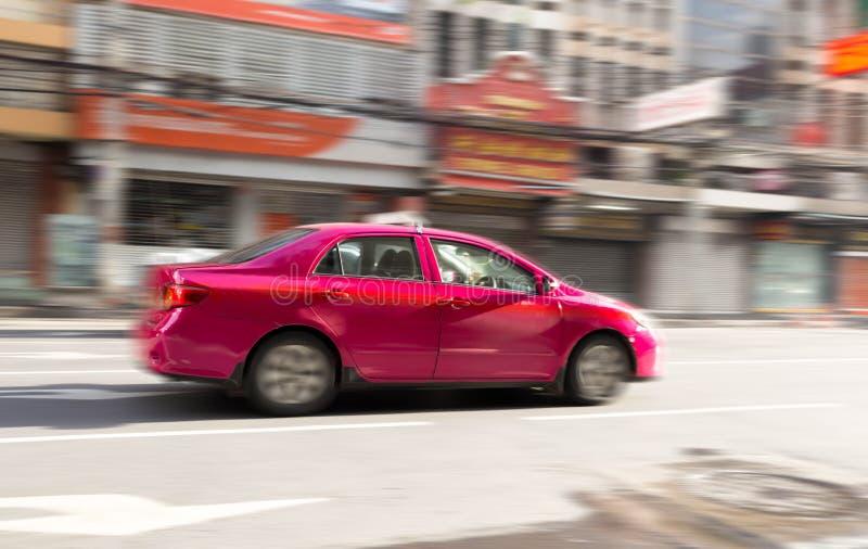 Verwischen Sie Bewegungskonzept des rosa Taxis auf der Straße stockbilder