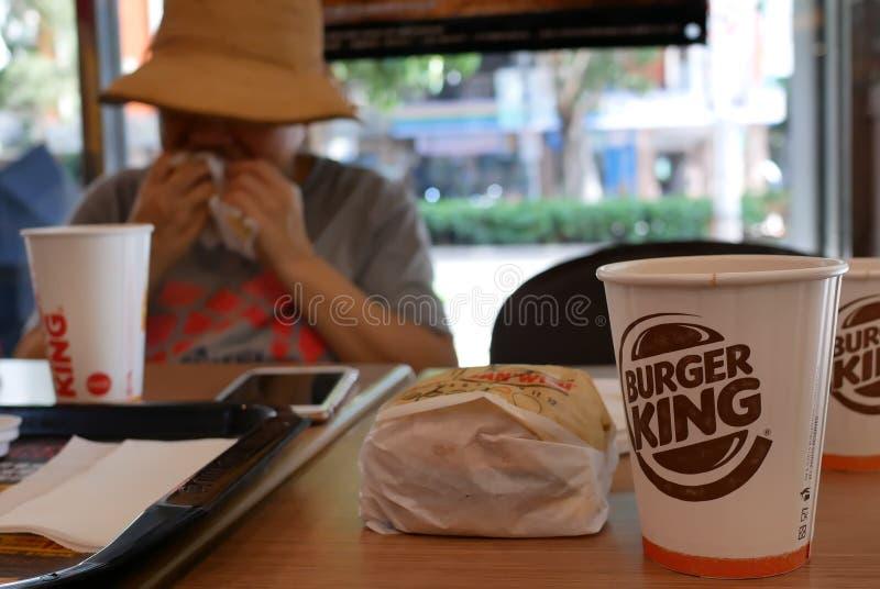 Verwischen Sie die Bewegung der Frau Burger essend und heißen Kaffee an Burger King-Schnellrestaurant trinkend lizenzfreie stockfotos