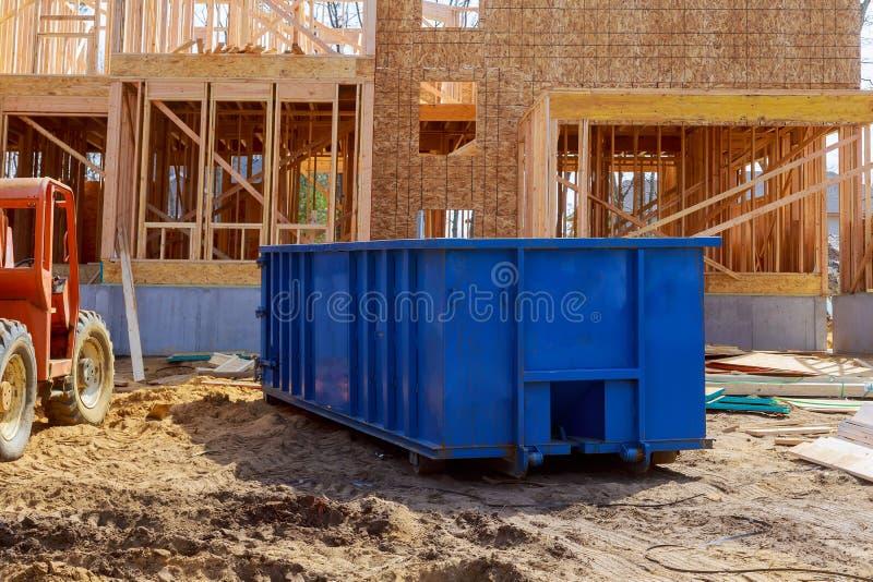 Verwischen Sie Müllcontainer, bereiten Sie Abfall und Mülltonnen nahe Neubaustandort des Apartmenthauserrichtens auf lizenzfreie stockbilder