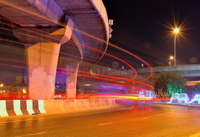 Verwischt den Verkehrsstrom in die Stadtnachtlichter eines Autos unter die Autobahn stockfoto