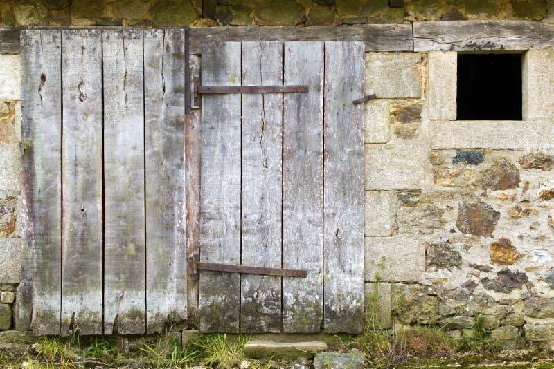 Verwitterte alte Scheunen-Tür und Steinwand stockbilder