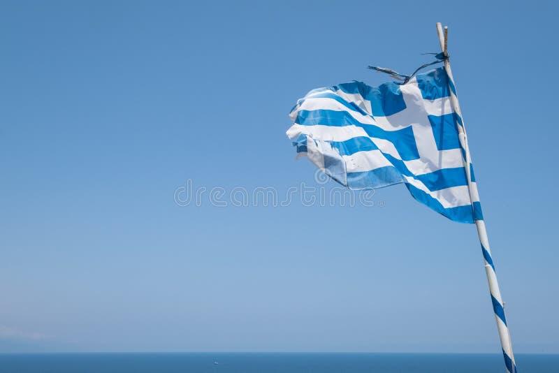 Verwitterte griechische Flagge, die im Wind durchbrennt lizenzfreie stockbilder