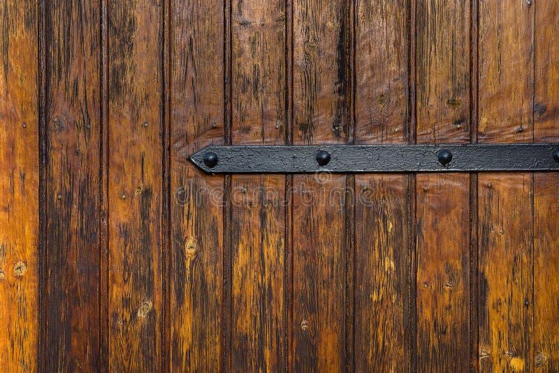 Verwitterte Planken-hölzerne Tor-Tür mit Schmiedeeisen-Scharnier-Klinke Dunkelbraune Earhy-Farbe Grungy gealterter Beschaffenheit stockfotografie