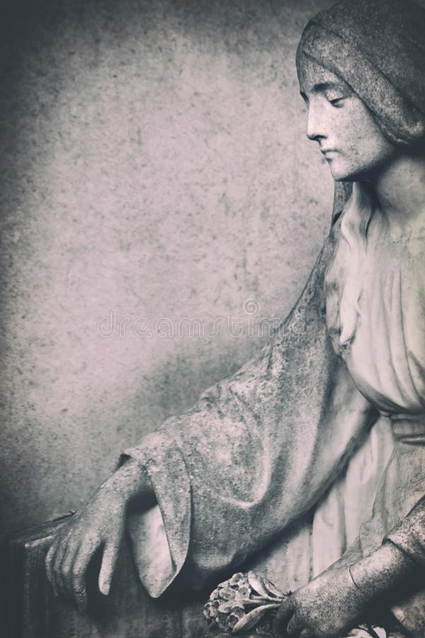 Verwitterte Stein-Maria-Statue auf Finanzanzeige lizenzfreie stockbilder