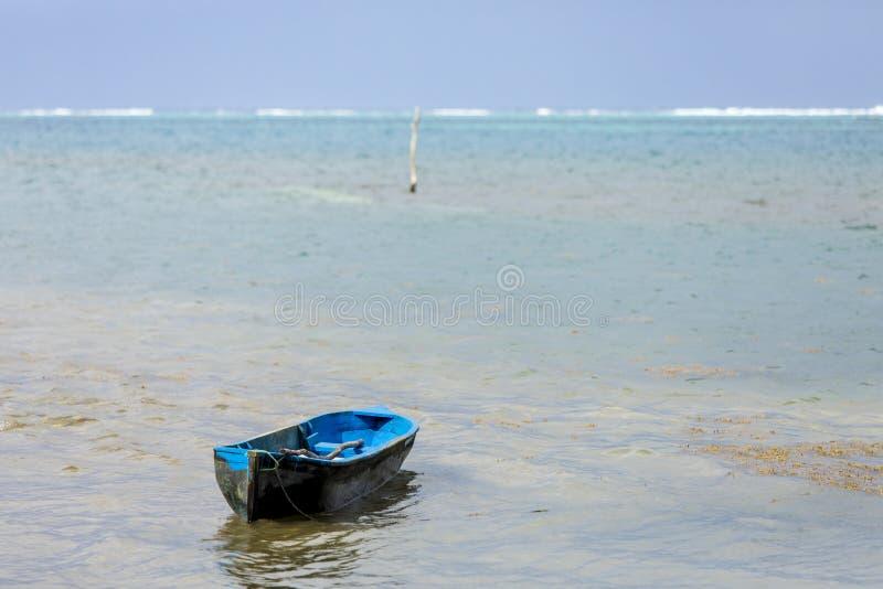 Verwittertes blaues Kanu, das in das Meer vor der Küste von Roatan schwimmt stockbild