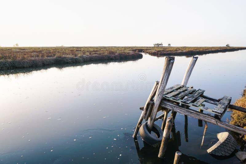 Verwittertes und gebrechliches hölzernes Dock, das fast in der Aveiro-Lagune einstürzt Schöne Ansicht des Wassers am hellen Tag lizenzfreies stockfoto