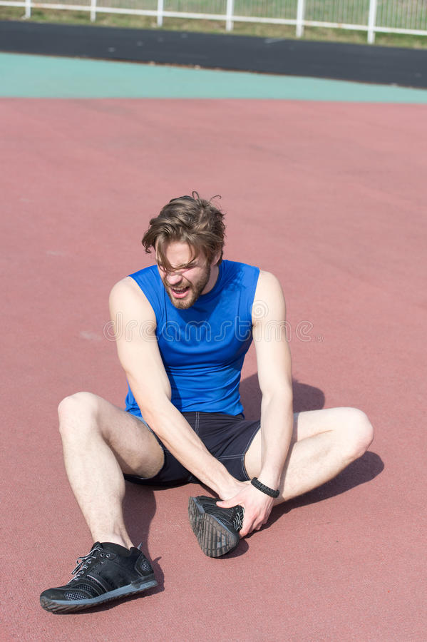 Verwonde agent die op renbaan pijn van gebroken been voelen royalty-vrije stock foto
