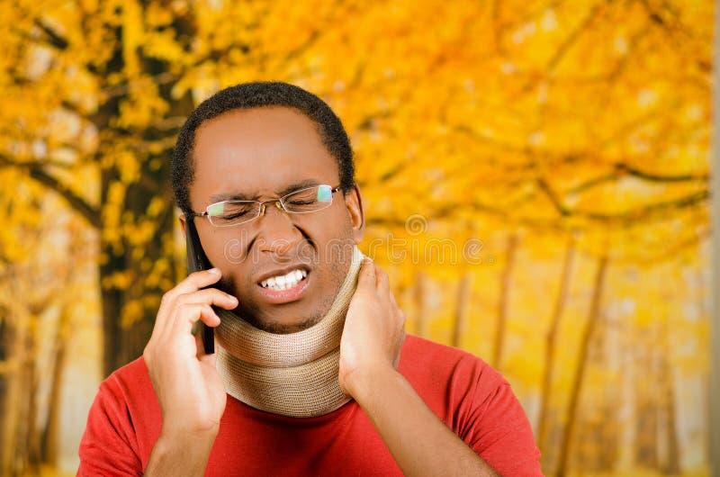 Verwonde jonge positieve zwarte Spaanse mannelijke dragende halssteun, die op telefoon en de steun van de handholding in ondraagl royalty-vrije stock foto