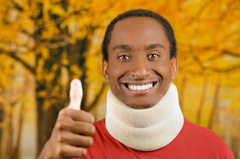 Verwonde jonge positieve zwarte Spaanse mannelijke dragende halssteun en het glimlachen aan camera die duim opgeven, gele samenva royalty-vrije stock foto