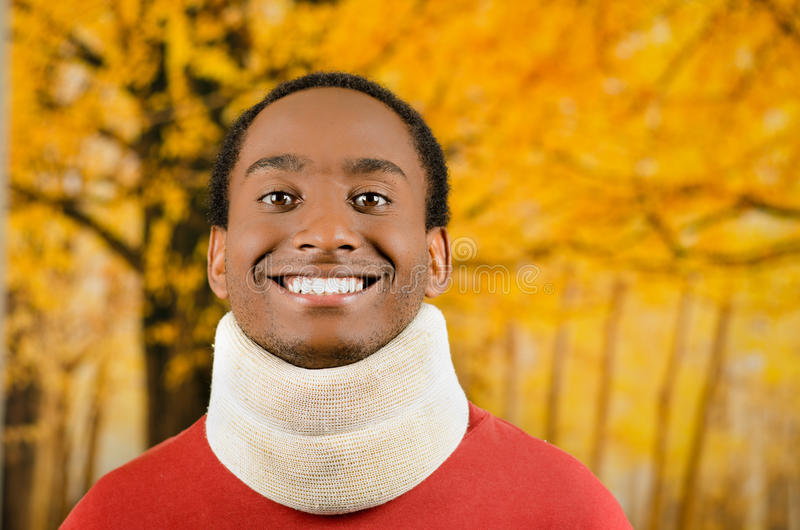 Verwonde jonge positieve zwarte Spaanse mannelijke dragende halssteun en het glimlachen aan camera, gele abstracte achtergrond royalty-vrije stock afbeeldingen