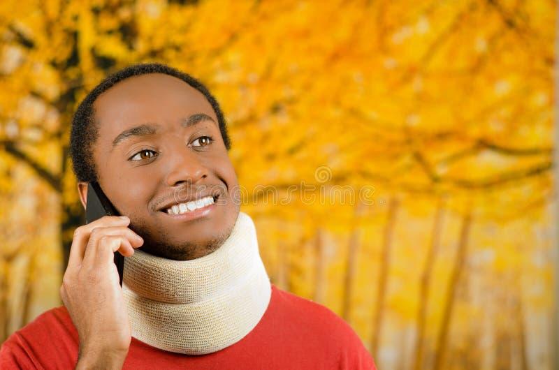 Verwonde jonge positieve zwarte Spaanse mannelijke dragende halssteun en het spreken op telefoon die, gele abstracte achtergrond  royalty-vrije stock fotografie