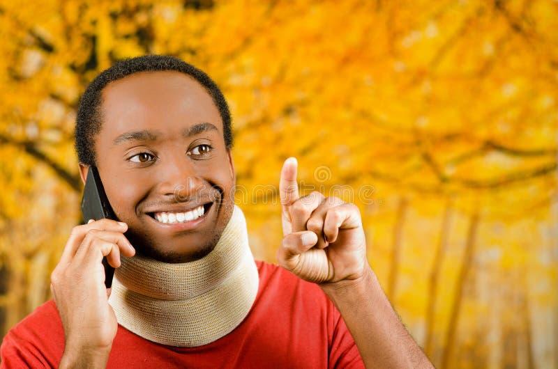 Verwonde jonge positieve zwarte Spaanse mannelijke dragende halssteun en het spreken op telefoon die, gele abstracte achtergrond  stock fotografie