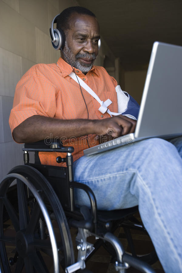 Verwonde Mens Gebruikend Laptop en Luisterend aan Muziek royalty-vrije stock foto's