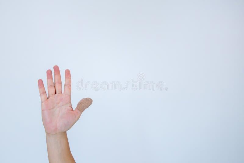 Verwonde pijnlijke vinger met wit verband De hand is verwond door het ongeval en het tonen van duim De duim is verpakt met a stock afbeeldingen