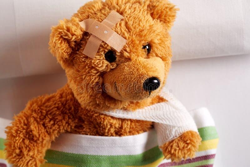 Verwonde teddybeer met verbonden wapen en hoofd stock foto