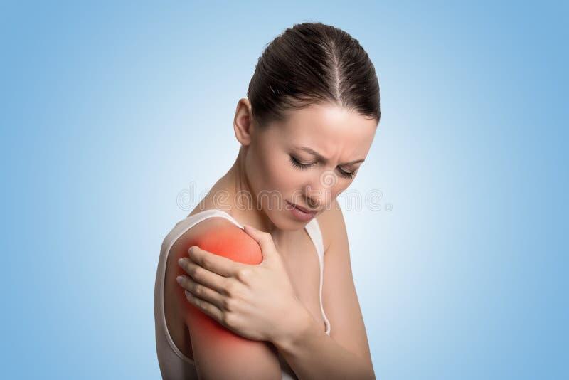 Verwonde verbinding Vrouwenpatiënt in pijn die pijnlijke die schouder hebben in rood wordt gekleurd royalty-vrije stock foto's