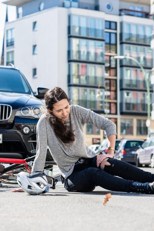 Verwonde vrouw met strenge die pijn door knieverstuiking wordt veroorzaakt na fietsongeval royalty-vrije stock foto