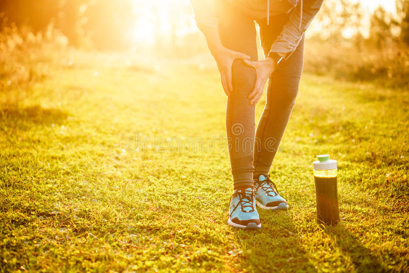 Verwondingen - sporten die knieverwonding op vrouw in werking stellen Detox smoothie stock foto
