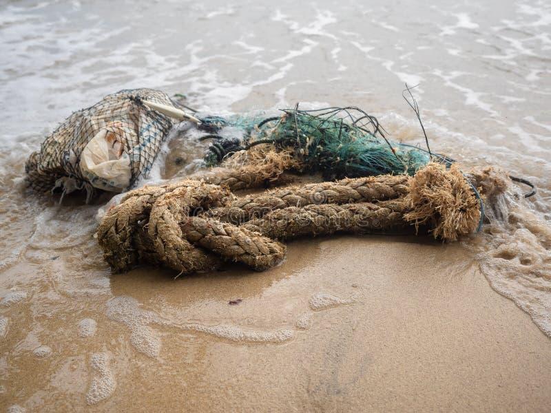 Verworpen visnet en kabel op het strand stock fotografie