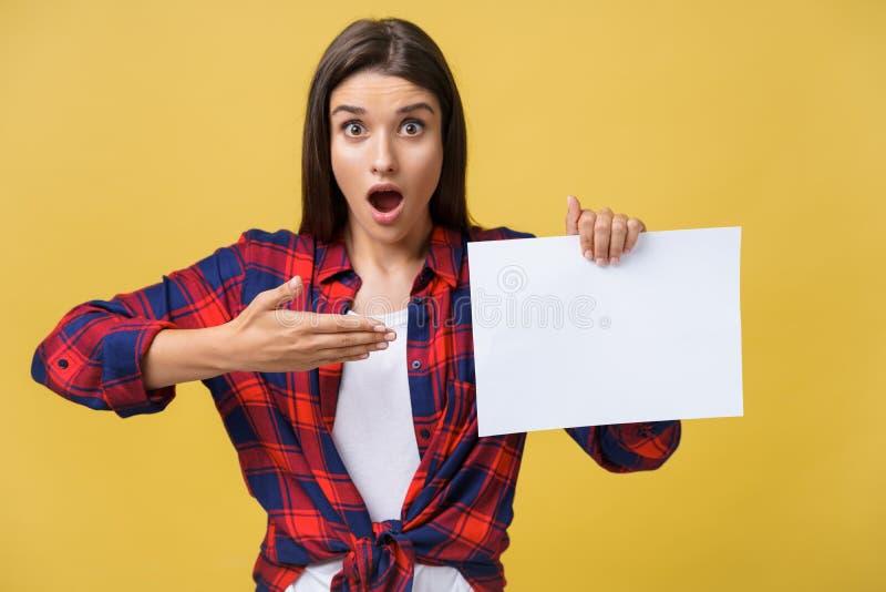 Verwunderung oder überraschte Frau mit der leeren weißen Platte, lokalisiert auf gelbem Hintergrund lizenzfreies stockbild