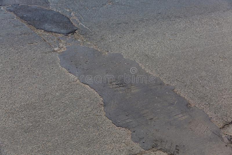 Very bad quality road with renovated potholes. Very bad quality road with potholes and puddles royalty free stock photo