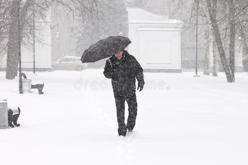 Very bad weather in a city in winter: terrible heavy snowfall and blizzard. Male pedestrian hiding from the snow under umbrella royalty free stock photo