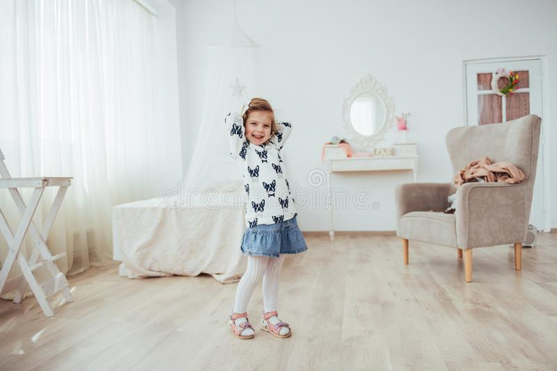 Very beautiful blonde charming little girl standing in the bright interior of the house, in full view stock photo