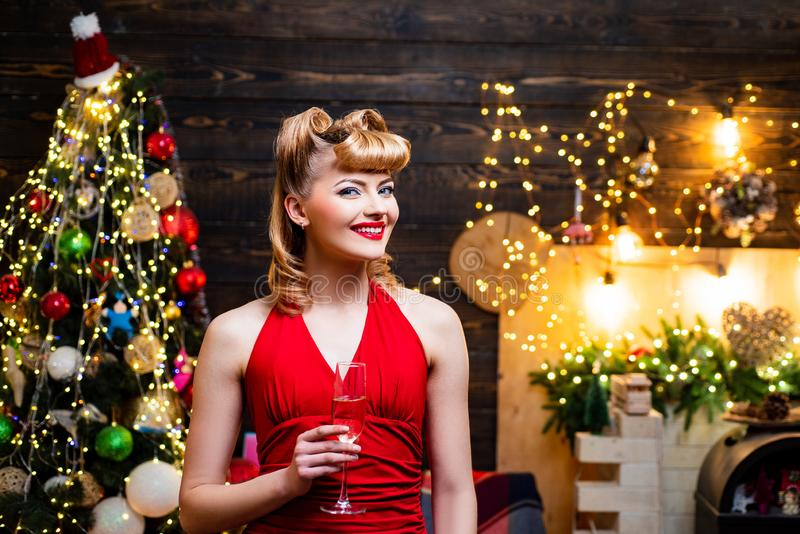 Very beautiful blonde girl over Christmas tree. Retro pin-up woman posing on vintage wooden Christmas background. stock photography