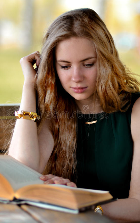 Blonde girl with long,light hair read interesting book outdoors stock photo