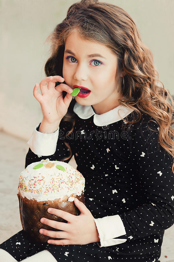 Studio portrait of sunny, beautiful, funny girl eating a cake royalty free stock photo