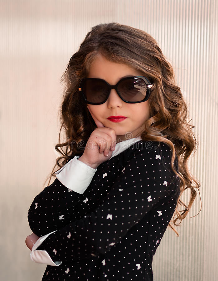 Portrait of a stylish fashion-dressed beautiful little girl in sunglasses stock photos