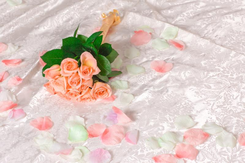 Very beautiful delicate pink roses with petals lie on the bed, a romantic bouquet of pink roses on white sheets stock photo