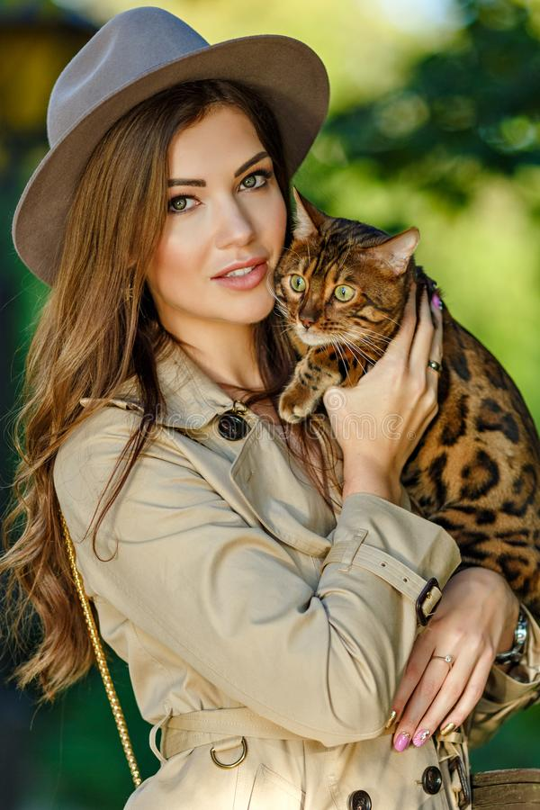 A very beautiful fashionable girl with a brown-haired hat in the. Hands of a Bengal cat, in a green park royalty free stock images