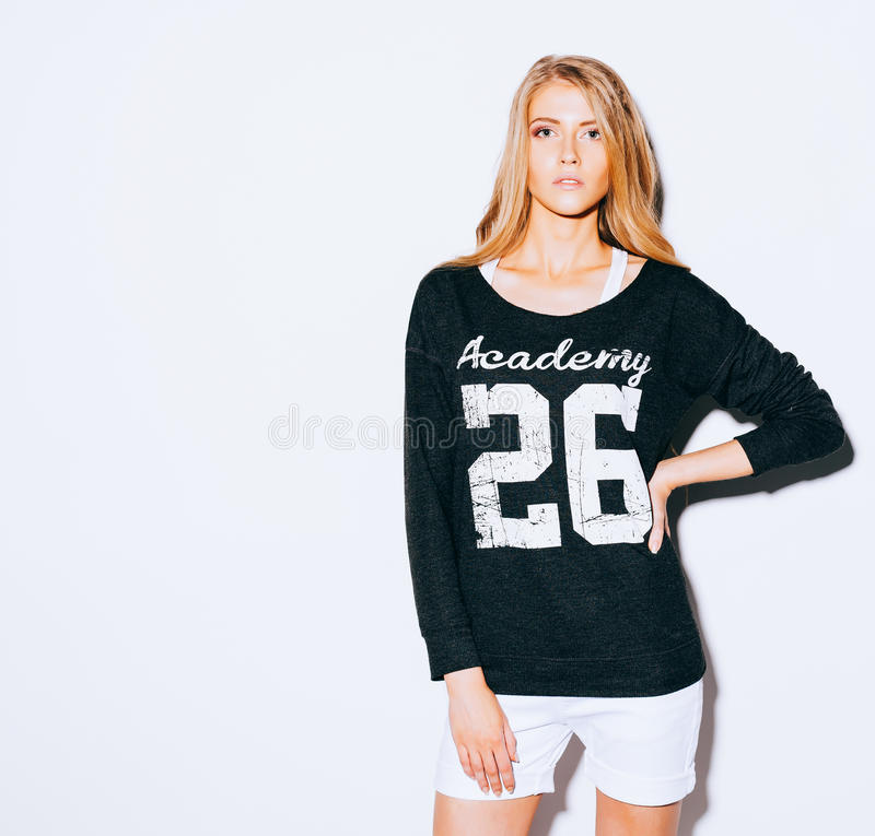 Very beautiful girl with long blond hair posing on a white background. Sweatshirt and white shorts. Indoor. Warm color. royalty free stock photography